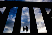 A young couple hold hands at the National Monument on Calton Hill in Edinburgh, Scotland