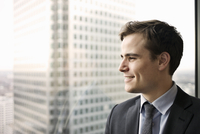 Portrait of young businessman looking out of office window