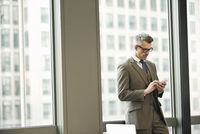 Businessman texting on smartphone in office