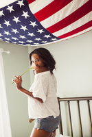 Young woman holding rose with US flag 11015242618  写真素材・ストックフォト・画像・イラスト素材 アマナイメージズ