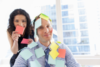 Female office worker covering male colleague with sticky notes