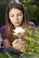 Teenage girl lying in grass looking at a daisy 11015242857| 写真素材・ストックフォト・画像・イラスト素材|アマナイメージズ