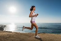 Mid adult woman jogging along cliff