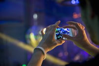 Man taking photograph in nightclub with cellular phone