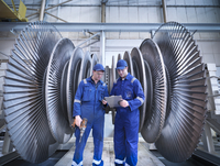 Engineers discussing notes in front of steam turbine in workshop