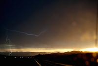 Car headlights on silhouetted highway during thunderstorm 11015244016| 写真素材・ストックフォト・画像・イラスト素材|アマナイメージズ