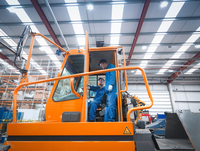 Engineers in cab of tow truck in truck repair factory