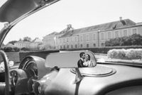 B&W image of mid adult bride and groom reflected in car mirror