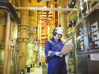 Female chemist reading notes in plant in power station