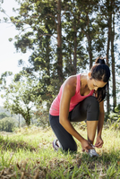 Female jogger tying shoelace in forest