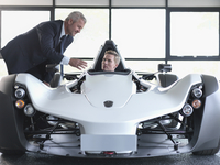 Salesman showing customer supercar in show room