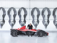 Engineer inspects supercar in factory with carbon fibre car body shells hanging on wall 11015245151| 写真素材・ストックフォト・画像・イラスト素材|アマナイメージズ