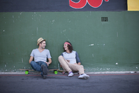 Two adult male friends sitting on skateboards chatting