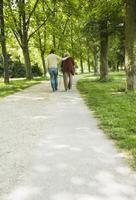 Senior woman and granddaughter walking through park, using walking stick