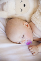 Baby girl sleeping in crib with cuddly toy
