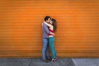 Romantic couple kissing in front of orange shutter