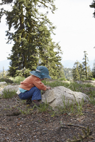 Toddler bending down to look at rock