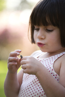 Close up portrait of girl holding lizard in garden