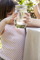 Girl holding jar with green anole lizard in garden
