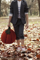 Cropped image of boy in forest holding pumpkin head
