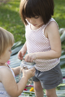 Girl and toddler sister holding jar with green anole lizard in garden