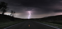 A single cloud-to-ground bolt lands at the end of a rural road, Lexington, Nebraska, USA