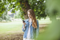 Young woman reading texts on smartphone in park