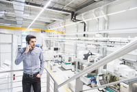 Male worker using mobile phone in tool manufacturing plant