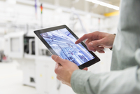 Male worker using digital tablet at tool manufacturing plant, focus on hands