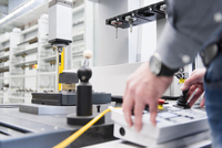 Factory worker hands operating control panel in factory