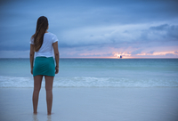Rear view of young woman looking out to sea at sunset, Boracay Island, Visayas, Philippines