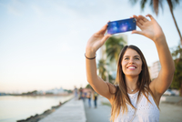 Young woman taking smartphone selfie on waterfront, Manila, Philippines