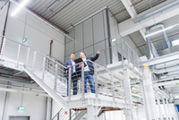 Businessman and manager on stairway in factory