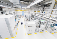 High angle view of manager walking along factory aisle
