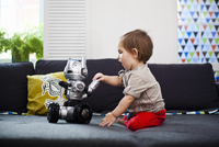 Male toddler playing with toy robot on sofa