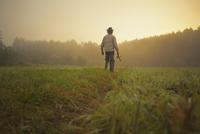 Mid adult man walking through field with fishing rod, Sarsy village, Sverdlovsk Region, Russia