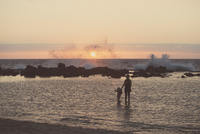 Silhouetted mother and female toddler paddling in sea looking out at waves splashing, Kona, Hawaii, USA