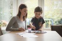 Boy smiling with mother as he paints on paper at table in living room