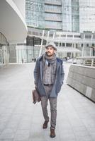 Businessman walking outside office buildings