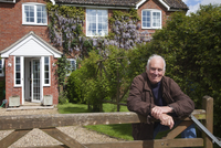 Senior man, leaning on garden fence 11015248570| 写真素材・ストックフォト・画像・イラスト素材|アマナイメージズ