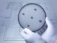 Gloved hands holding silicon wafer in laboratory, close up