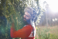 Young man carrying Christmas tree on shoulders in woods 11015248821| 写真素材・ストックフォト・画像・イラスト素材|アマナイメージズ