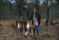 Young hiking couple with lanterns walking dog in woods