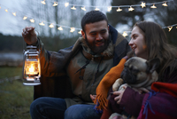 Young camping couple with dog wrapped in blanket