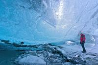Mature man exploring crystal ice cave, Breidamerkurjokull, Vatnajokull, Iceland