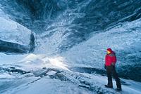 Mature man looking over shoulder whilst exploring crystal ice cave, Breidamerkurjokull, Vatnajokull, Iceland