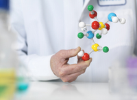 Scientist holding a molecular model of a chemical formula