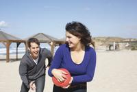 Young couple running with ball on beach, Tel Aviv, Israel 11015249072| 写真素材・ストックフォト・画像・イラスト素材|アマナイメージズ