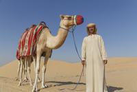 Portrait of bedouin with camel in desert, Dubai, United Arab Emirates