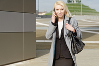 Businesswoman, walking outdoors, using mobile phone